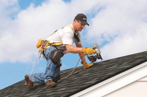 Worker repairing hail damage on shingle home in Manassas, Virginia - Manassas Roofing Experts